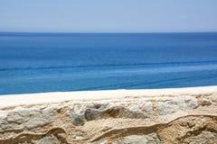Brun stenvägg nära det blåa havet Fotografering för Bildbyråer