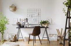 Brun stol på skrivbordet med lampan i den vita workspaceinre med p fotografering för bildbyråer