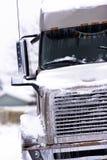 Brun stor modern halv lastbil i snö och is Royaltyfri Bild