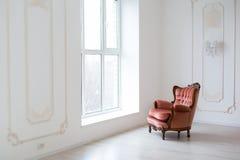 Brun tappningstilstol i klassiskt inre rum med det stora f?nstret arkivfoton