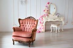 Brun tappningstilstol i klassiskt inre rum med det stora f?nstret royaltyfri foto