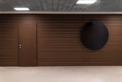 Brun vägg med dörr- och mellanrumsrundastället för en text i affärsmitt Arkivfoton
