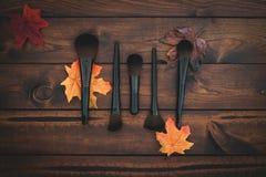 Brun wood bakgrund med blandade makeupborstar royaltyfri foto