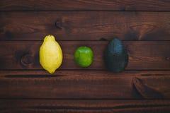 Brun wood bakgrund med den visade avokadot, citronen och limefrukt fotografering för bildbyråer