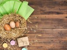 Bruna ägg i bakgrund för eco för hörede lantlig med brunthönaägg, sugrör, färgat stearinljus för gåvaask och papper på Arkivfoto
