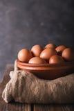 Bruna ägg i en brun keramisk bunke på att plundra och trätabell på grånar abstrakt bbackground Lantlig stil Ägg liten flicka och  Royaltyfri Bild