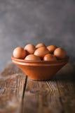 Bruna ägg i en brun keramisk bunke på trätabellen på grånar abstrakt bbackground Lantlig stil Ägg Påskfotobegrepp Royaltyfri Foto