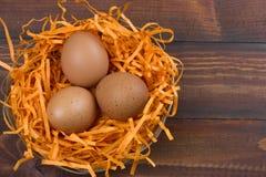 bruna ägg i ett dekorativt rede på en träbakgrund royaltyfri foto