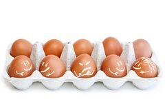 10 bruna ägg i formen för ägg med roliga lyckliga och ilskna målade framsidor som isoleras på vit arkivbild