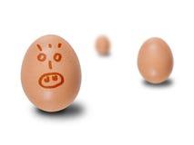 Bruna ägg med drog framsidor Royaltyfri Foto
