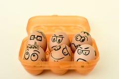 Bruna ägg med roliga framsidor Royaltyfri Fotografi