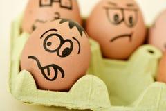 Bruna ägg med roliga framsidor Royaltyfri Foto