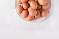 Bruna ägg på en vit platta på en vit bakgrund Ägg Påskfotobegrepp Fotografering för Bildbyråer