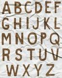 Bruna alfabetbokstäver på skrynkligt papper Fotografering för Bildbyråer