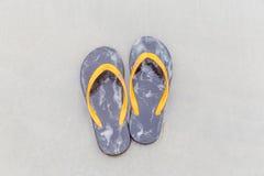 Bruna badskor på sandig havstrand-, sommar- och semesterconce arkivfoto