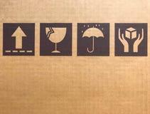 Bruna bräckliga symboler på papp eller lådan Arkivfoto