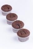 Bruna chokladmuffin som är ordnade över vit bakgrund Royaltyfria Foton
