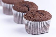 Bruna chokladmuffin som är ordnade över vit bakgrund Royaltyfri Fotografi