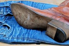 Bruna cowboykängor på jeans Arkivfoto