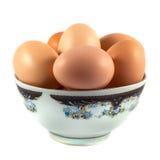 Bruna fega ägg i en kopp som isoleras på vit Arkivfoton