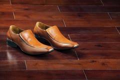 Bruna formella skor på ett Wood golv Fotografering för Bildbyråer