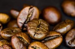 Bruna grillade kaffeb?nor p? svart bakgrund, slut upp, makro arkivbild