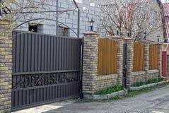 Bruna järnportar och ett staket av tegelstenar och bräden på gatan nära vägen Royaltyfria Foton