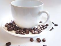Bruna kaffebönor i en vit kopp Royaltyfri Foto