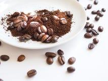 Bruna kaffebönor och jordkaffe på en vit kopp Arkivfoto