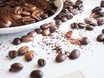 Bruna kaffebönor och jordkaffe på en vit kopp Arkivbild