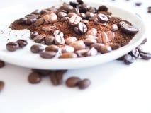 Bruna kaffebönor och jordkaffe på en vit kopp Arkivfoton