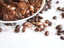 Bruna kaffebönor och jordkaffe på en vit kopp Arkivbilder