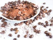 Bruna kaffebönor och jordkaffe på en vit kopp Fotografering för Bildbyråer