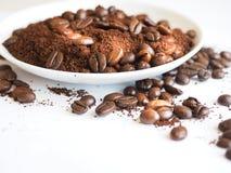 Bruna kaffebönor och jordkaffe på en vit kopp Royaltyfri Foto