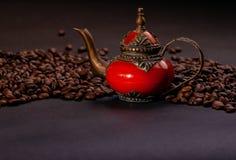 Bruna kaffekorn på en svart bakgrund med kopieringsutrymme och den tradatsionny forntida orientaliska tekannan Royaltyfria Foton