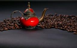 Bruna kaffekorn på en svart bakgrund med kopieringsutrymme och den tradatsionny forntida orientaliska tekannan Fotografering för Bildbyråer