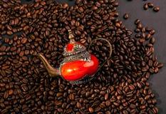 Bruna kaffekorn på en svart bakgrund med kopieringsutrymme och den tradatsionny forntida orientaliska tekannan Royaltyfria Bilder