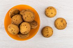 Bruna kakor i orange bunke och på trätabellen Royaltyfri Foto