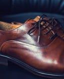 Bruna lädermäns skor med träskon Arkivbilder