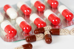 Bruna och vit-och-röda antibiotiska kapslar Arkivbild
