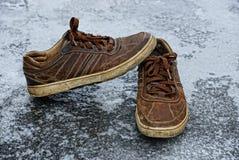 Bruna skor för man` s i gården på isen Royaltyfri Bild