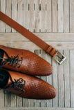 Bruna skor för man` s med snör åt på en träbakgrund och en brunt Fotografering för Bildbyråer