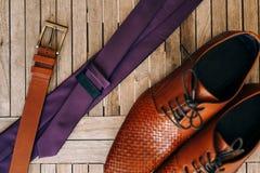 Bruna skor för man` s med snör åt på en träbakgrund och en brunt Arkivbilder
