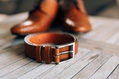 Bruna skor för man` s med snör åt på en träbakgrund och en brunt Arkivbild