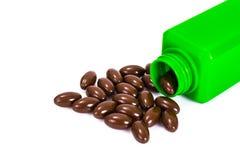 Bruna växt- kapslar i en grön flaska en alternativ medicin Arkivfoton