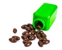 Bruna växt- kapslar i en grön flaska en alternativ medicin Royaltyfria Foton
