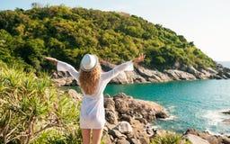 Brunbränd brunett som lyfter armar och tycker om frihet vid havet Royaltyfri Foto