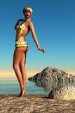 Brunbränd kvinna i prickgulingbaddräkt på stranden Royaltyfri Foto