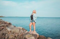 Brunbränd kvinna som poserar på stranden på sommardagen som ser upp Den drömlika kvinnlign i jeanskläder, stående stenig kust, sl Fotografering för Bildbyråer