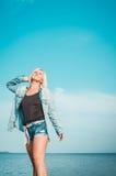 Brunbränd kvinna som poserar på stranden på sommardagen som ser upp Den drömlika kvinnlign i jeanskläder, stående stenig kust, sl Arkivfoto